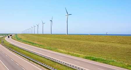 Wind energy windmills near highway and sea shore Stock Photo - 21077619