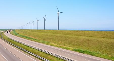Wind energy windmills near highway and sea shore Stock Photo - 21077619