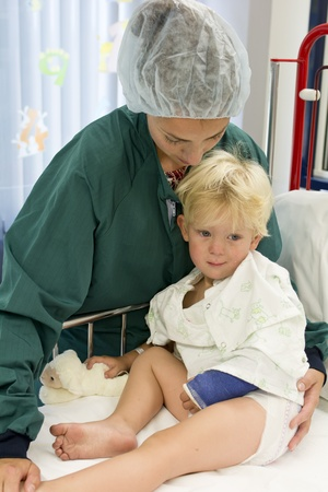 Little boy in hospital going into surgery with caring mother photo