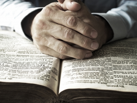 Man with his hands praying on old bible closeup