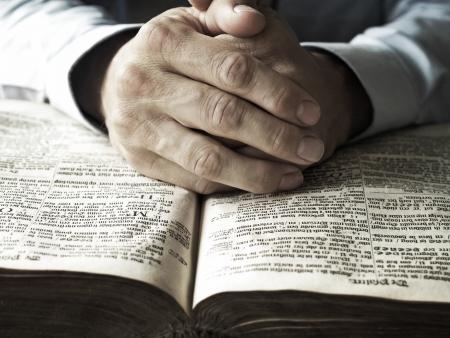 bible ouverte: L'homme avec ses mains en priant sur la vieille bible gros plan