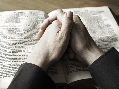 baptist: Man with his hands praying on old bible closeup