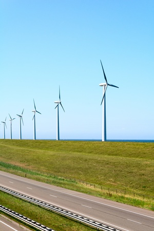 Alternative energy by windmills near road photo