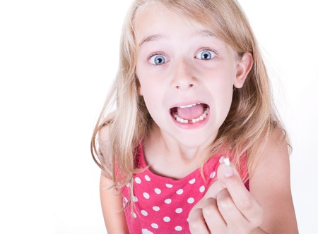 Girl showing or holding first missing tooth