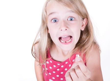 Muchacha que muestra la primera o la celebración de diente que falta Foto de archivo