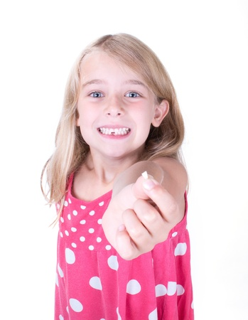 tooth fairy: Girl showing or holding first missing tooth