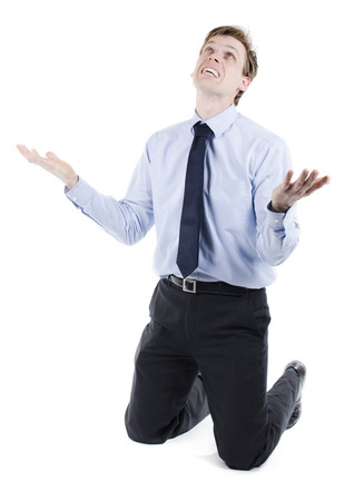 Emotional businessman on his knees begging for help or praying Stock Photo