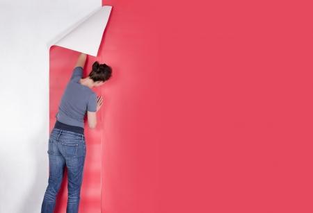 Woman hanging red wallpaper