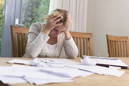 budget crisis: Woman with financial problems looking at bills Stock Photo
