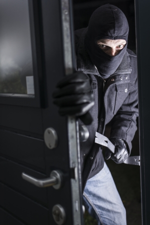 Burglar entering a residential house in the evening