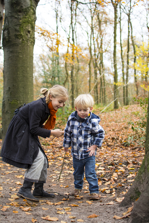 Little boy and girl playing in the woods photo