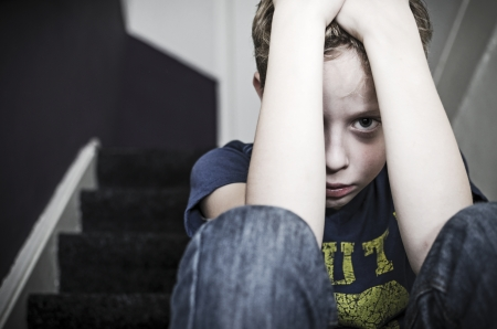 階段の上の孤独な悲しい少年