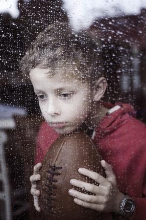 Eenzame jongen kijkt door raam in de regen