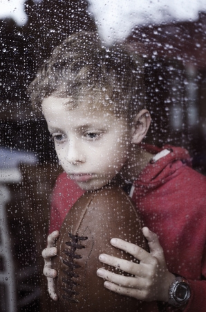 Lonely boy looking through window at rain