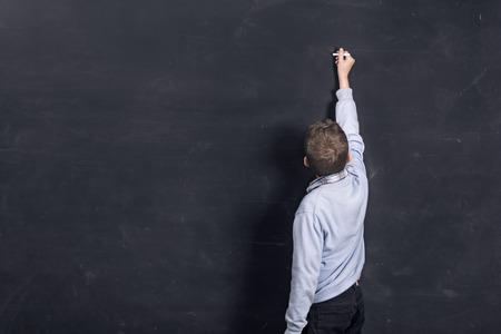 Boy writing on black chalkboard  Copy space