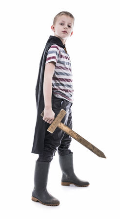 Little kid dressed up as knight with wooden toy sword  Concept of bravery  Stock Photo
