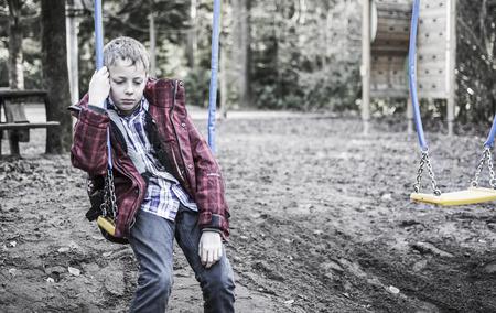 Verdrietig of eenzame jongen op de schommel in de speeltuin Stockfoto