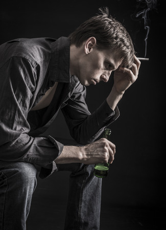economic depression: Smoking, beer drinking, depressed man thinking