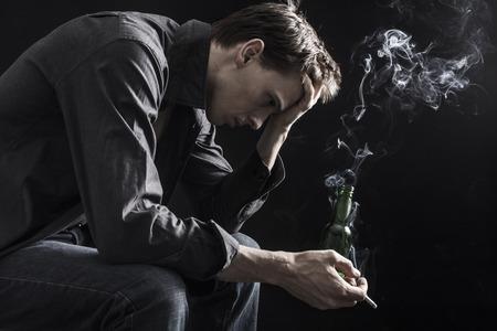 Depressed man smoking cigarette