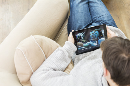 Man at home watching movie on tablet pc