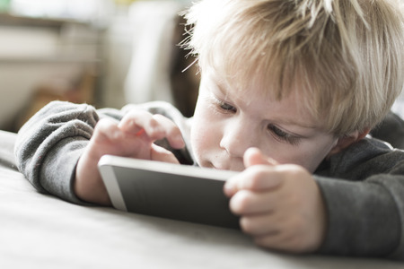 little kid playing game on smart phone