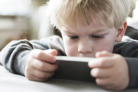 Boy playing on smartphone photo