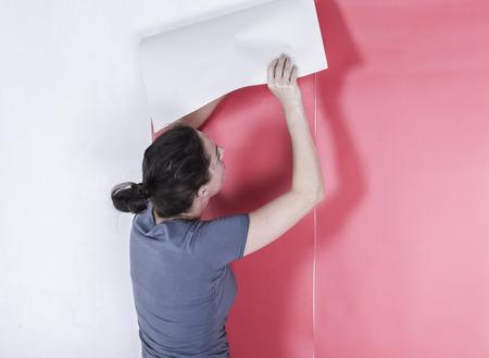Vrouw opknoping behang verfraaien van de muur