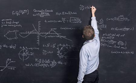 profesor: Niño elegante que hace matemáticas en la pizarra