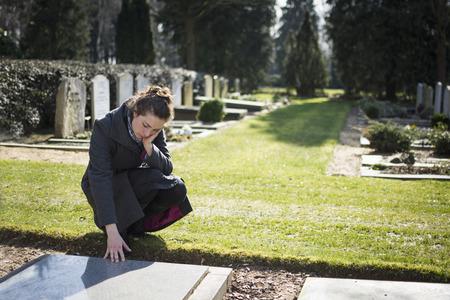 Frau sitzt am Grabstein auf Friedhof Standard-Bild - 26559182