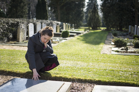 Nő ül a sírkő a temetőben