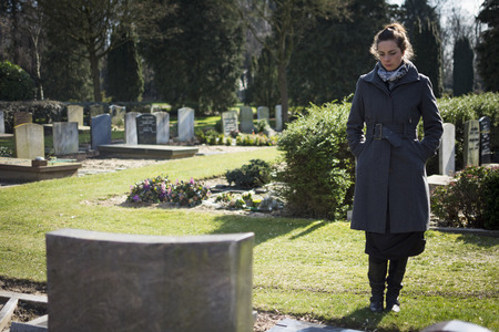 Widow standing at graveyard looking at grave