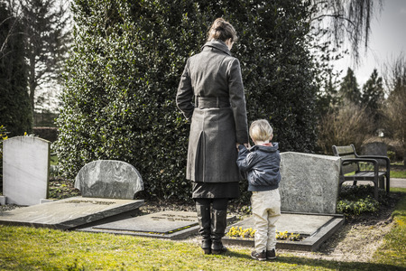 mourn: donna e bambino guardando pietra tombale sul cimitero