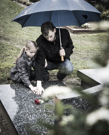 Father and child sitting at gravestone on graveyard Stock Photo