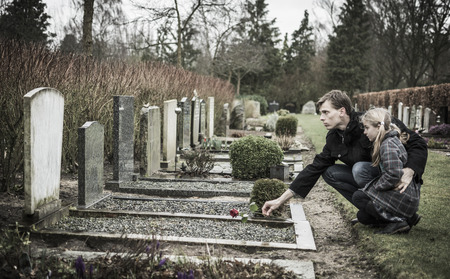 Father and child looking at gravestone on graveyard