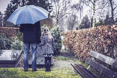Father and daughter at grave
