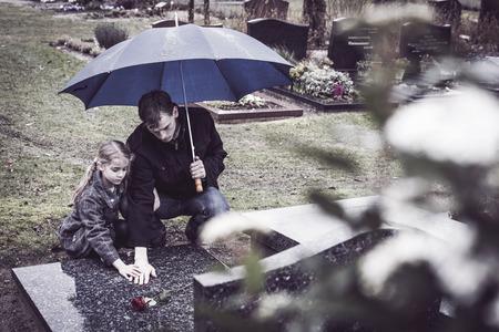 weduwnaar en zijn doughtier op kerkhof 's moeders grafsteen