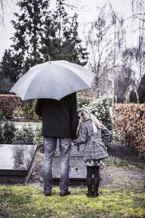 girl in rain: Father and daughter at grave