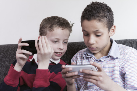 Two boys playing games on a smartphone. photo