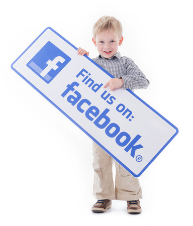 Little boy holding Facebook sign