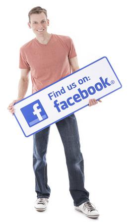 Man holding Facebook Find us sign