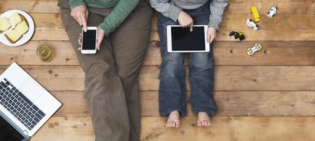 Moeder en zoon met behulp van tablet en laptop