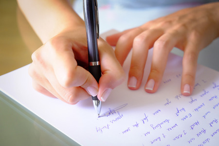 writing on paper: writing a letter with a black pen Stock Photo