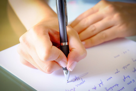 girl writing a letter with a black pen Stockfoto