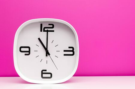party time: Modern white clock isolated on pink background