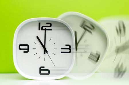 timezone: Modern white clock on light green background in motion Stock Photo