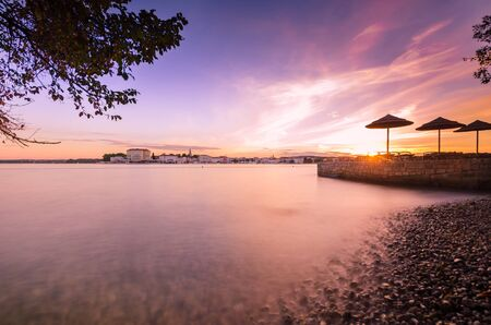sunrise: Morning by the coast looking at sunrise at old town of Porec - Croatia Stock Photo