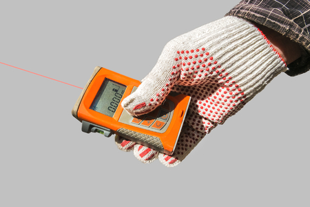 Laser measurement. A hand in a working glove holding a laser meter against a white sound-insulating wall. An authentic working environment.