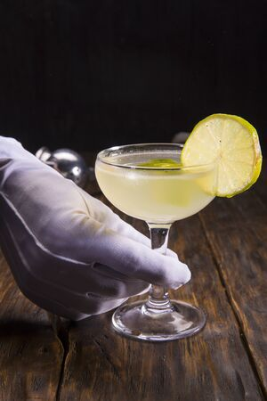 Lemon cocktail with mint on a dark wooden background