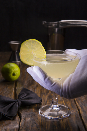 Lemon cocktail with a lemon piece on a dark wooden background with accessories