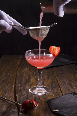 The strawberry cocktail with a strawberry piece filtered through a sieve